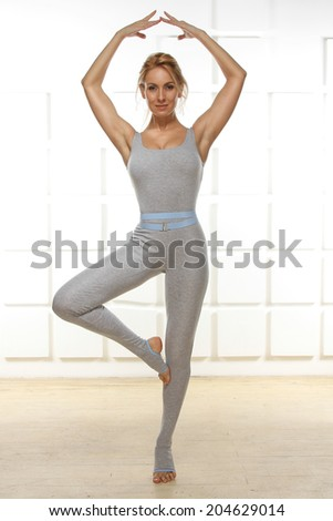 Beautiful sexy blonde with perfect athletic slim figure engaged in yoga, exercise or fitness, lead a healthy lifestyle, dressed in comfortable casual clothes ballerina standing in a pose of hands up - stock photo