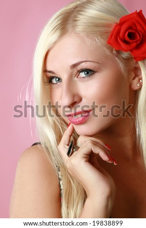 Beautiful sexy blonde with red flower in hair on pink background