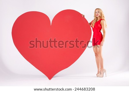 Beautiful sexy blonde woman posing with big red heart. St. Valentine's Day. Studio shot. - stock photo