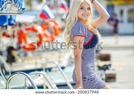 Beautiful sexy blonde woman wearing sailor striped dress posing near boats  - stock photo