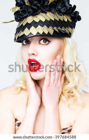Beautiful sexy blonde woman with red lips in extravagant hat. Beauty fashion model girl portrait with necklace and elegant hat, isolated on a white background