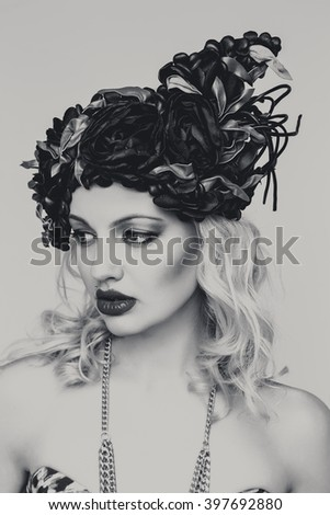 Beautiful sexy blonde woman with red lips in extravagant hat. Beauty fashion model girl portrait with necklace and elegant hat, isolated on a white background. Black and white photo