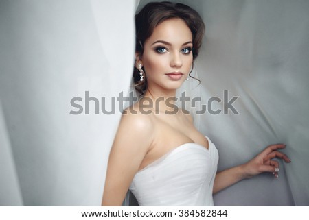 Beautiful sexy bride in white dress posing under curtain - stock photo