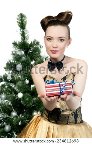 Beautiful sexy brunette girl in a gold dress at the Christmas tree with a gift on a white background isolated - stock photo