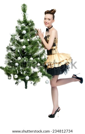 Beautiful sexy brunette girl in a gold dress the Christmas tree on a white background isolated