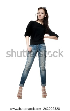 Beautiful sexy brunette girl in jeans and a black sweater posing on a white background isolated - stock photo