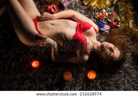 Beautiful sexy brunette girl in red underwear lying in a Christmas tree - stock photo
