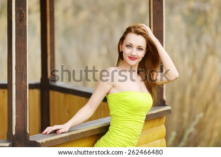 beautiful sexy brunette girl in short yellow dress with, red high heel shoes, with big Breasts and long legs on the street in the Park sitting on a wooden bridge near the lake. Spring, Summer  walk. - stock photo