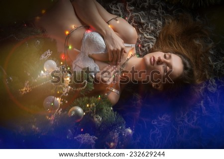 Beautiful sexy brunette girl in white underwear lying in a Christmas tree - stock photo