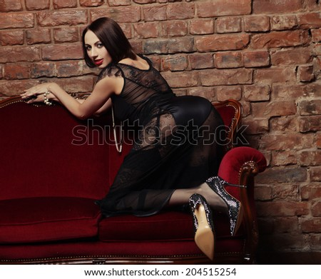Beautiful sexy brunette girl on sofa