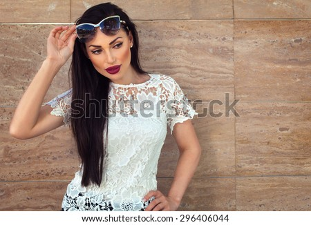 Beautiful sexy brunette model woman in sunglasses on a beige background copy space. Summer woman fashion concept - stock photo