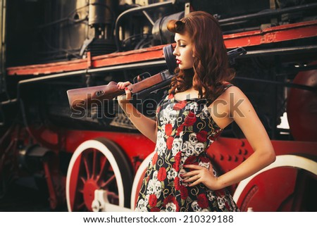 Beautiful sexy brunette retro woman with pin-up hairstyle and make-up in a shorts and shirt with a gun in her hands on vintage train. Outdoors. Retro toned - stock photo