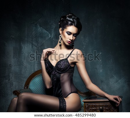 Beautiful sexy brunette wearing alluring lingerie and jewelry in retro interior.