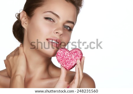 Beautiful sexy brunette woman eating cake shape of heart on a white background, healthy food, tasty, organic, romantic valentines day - stock photo