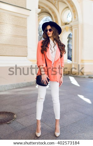 Beautiful  sexy brunette young lady with perfect slim body, long legs ,  bright make up, amazing wavy hairstyle. Model walking on summer day  on the street. White hight heels. Casual style. - stock photo
