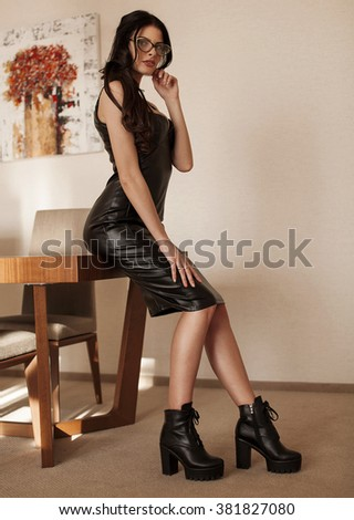 Beautiful sexy brunette young woman wearing black leather short dress sitting on bed. Fashionable female with attractive body posing provocatively, indoor. Sensual girl with big boobs. - stock photo
