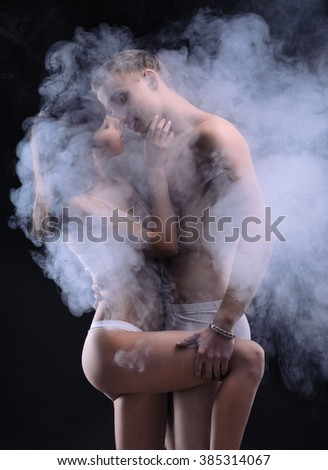 Beautiful sexy couple in love. Both of them in underwear. Photo in the dark with smoke on the background.