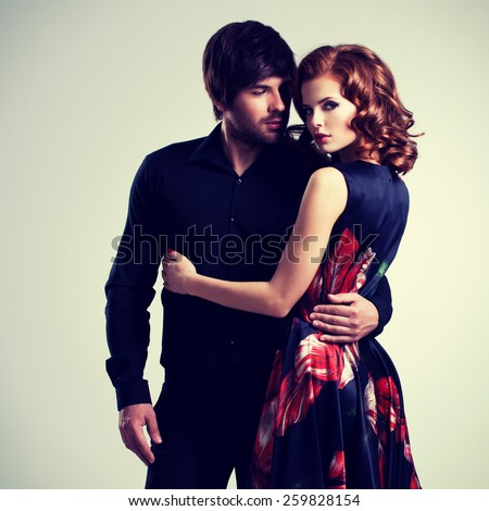 Beautiful sexy couple in love standing on gray background.