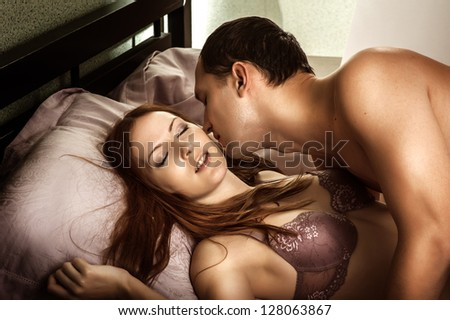 Beautiful sexy couple of  lovers. Young man kissing woman in darkness bedroom on bed