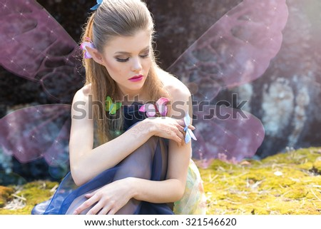 beautiful sexy cute gentle girl elf butterfly sits in a clearing in the woods in the sun light with butterflies on her hair and arm with bright makeup - stock photo