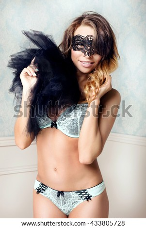 Beautiful sexy dancer with perfect slim body posing in lingerie and black mask.