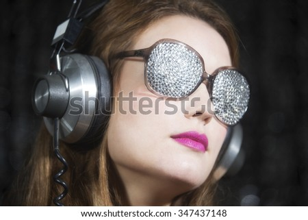 beautiful sexy disco woman, listening to music with sparkle covered sunglasses. Perfect for stylish club, disco and fashion events  - stock photo