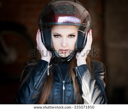 Beautiful sexy elegance haired hair woman driver, has happy fun cheerful smiling face, black leather jacket, motorcycle helmet, brown smokey eyes. Has slim sport body. Portrait street urban.  - stock photo