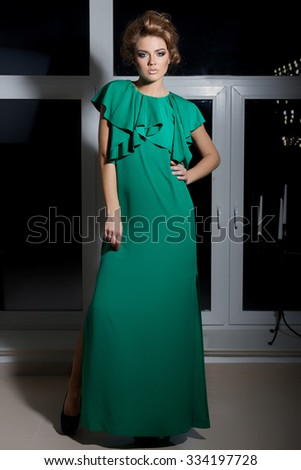 beautiful sexy elegant long-legged girl in a long green evening dress with evening hairstyle and bright make-up, new year's evening look - stock photo
