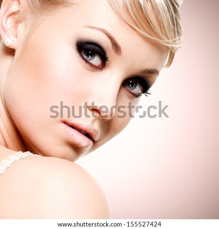 Beautiful sexy face of young woman with black eye makeup - stock photo