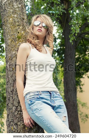beautiful sexy girl blonde in the Park in sunglasses with large plump lips standing near a tree - stock photo