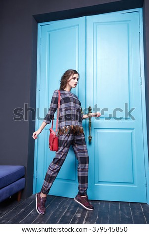 Beautiful sexy girl dressed style of fashion clothing new catalog of the collection, modern, stylish trouser suit in a cage with feathers sneakers accessory, interior room with blue door entrance exit