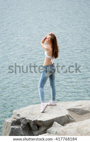 Beautiful sexy girl in a bathing suit and jeans on a rocky shore - stock photo