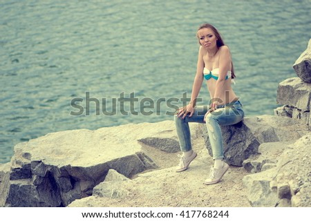Beautiful sexy girl in a bathing suit and jeans on a rocky shore