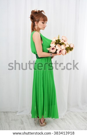 Beautiful sexy girl in a green dress and with flowers in her hands posing on white background isolated in Studio - stock photo