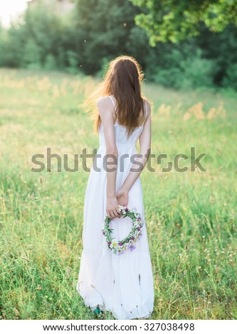 beautiful sexy girl in a long white dress with a wreath in the hands of enjoying a walk in the park at sunset - stock photo