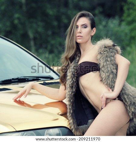 Beautiful sexy girl in bikini and in fur cape posing on a background of golden car. sexy lady near the golden car. in vintage colors.