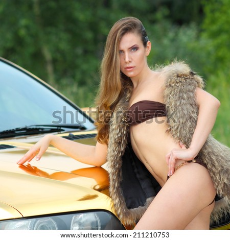 Beautiful sexy girl in bikini and in fur cape posing on a background of golden car. sexy lady near the golden car.