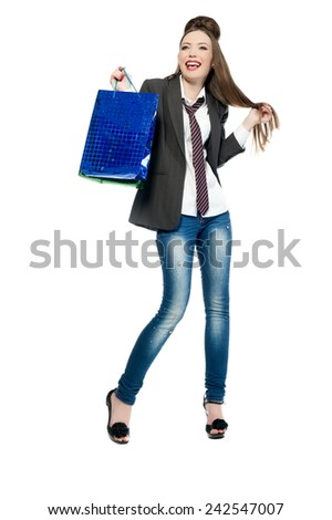 Beautiful sexy girl in jeans and a jacket and tie with shopping bags posing on a white background isolated