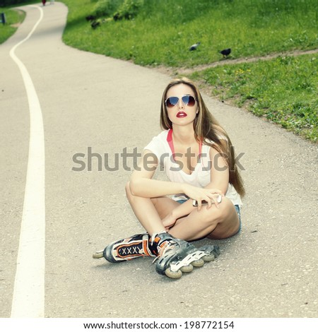 beautiful sexy girl in sunglasses on roller skates. In vintage colors. Outdoor lifestyle.
