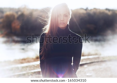 Beautiful sexy girl on the street against the sun - stock photo