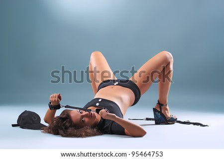 Beautiful sexy girl police pistol and handcuffs, on a blue background - stock photo