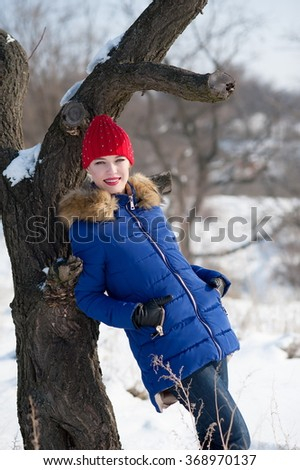 Beautiful sexy girl posing in a winter snow-covered forest