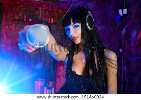 Beautiful sexy girl singing on a party in the old garage. - stock photo