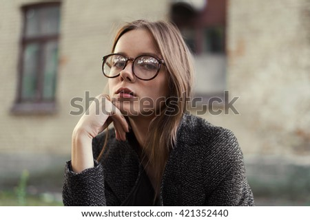 beautiful sexy girl wearing glasses on a city street
