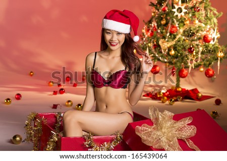 Beautiful sexy girl wearing santa claus clothes inside wrapped christmas gift box
