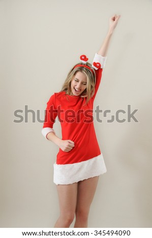 beautiful sexy girl wearing santa claus clothes show succes gesture; xmas concept; studio shoot over grey - stock photo