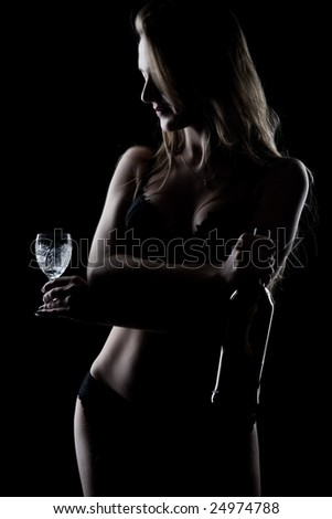 Beautiful sexy girl with a bottle of wine on a black background