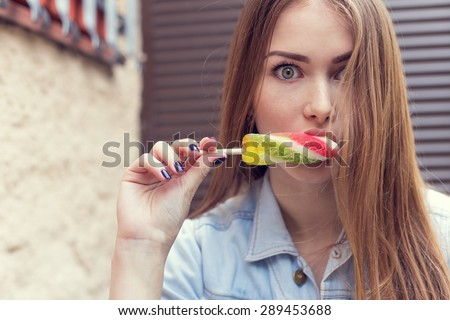 beautiful sexy girl with big eyes and long red hair eating a delicious ice cream color on the stairs - stock photo
