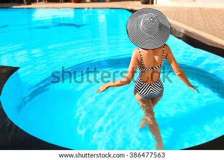 Beautiful Sexy Girl With Healthy Skin In Elegant Striped Bikini, Sun Hat Relaxing In Swimming Pool Water In Resort Spa Hotel On Travel Holidays Vacation.
