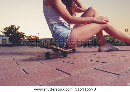Beautiful sexy girl with long legs in jeans shorts sits on skateboard on red paved surface back side view, warm toned image